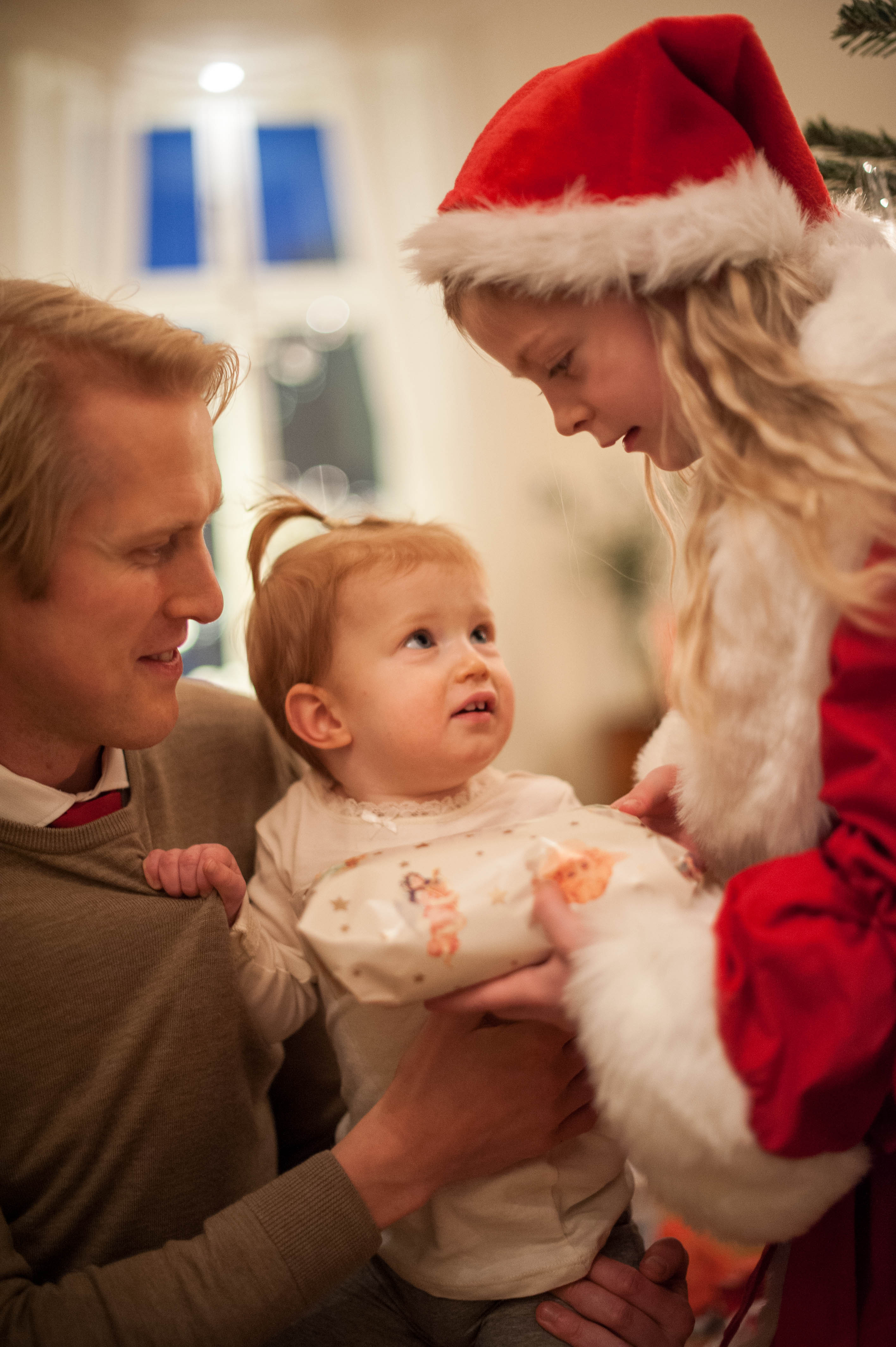 My niece met Santa for the first time. A year ago this photo would not have made the cut since she looks more worried than happy. I now think it captures the moment, the little hand holding her father's sweater, and the other's heads framing her beautifully.