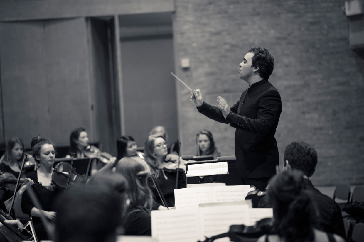 Jamie Phillips conducting the orchestra at West Road Concert Hall