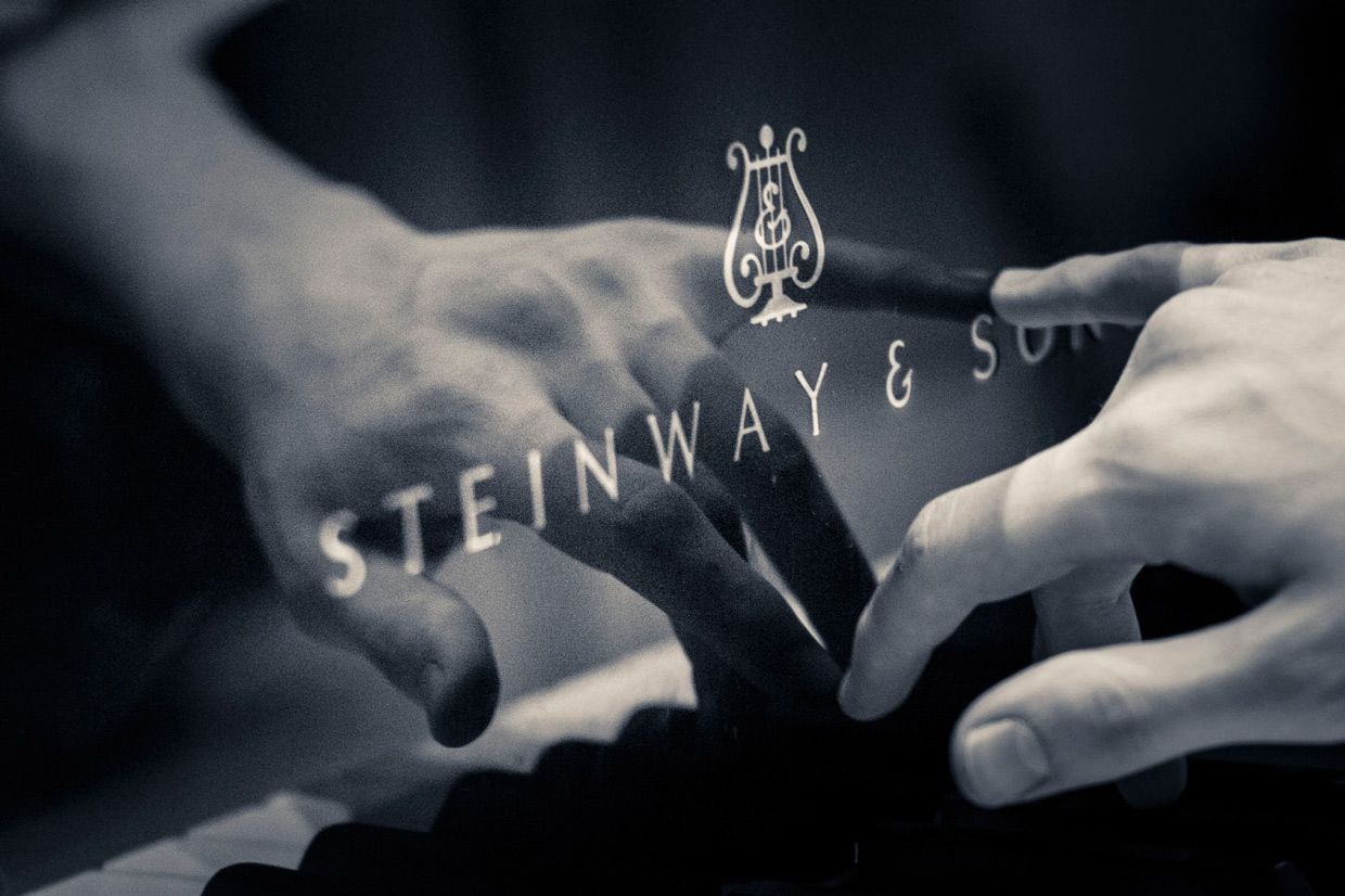The pianist's hand reflected in the black wood of a Steinway & son piano