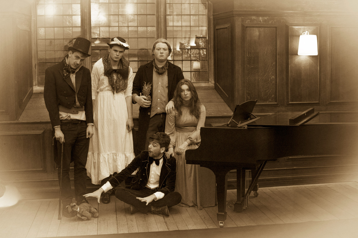 The cast sitting by a piano