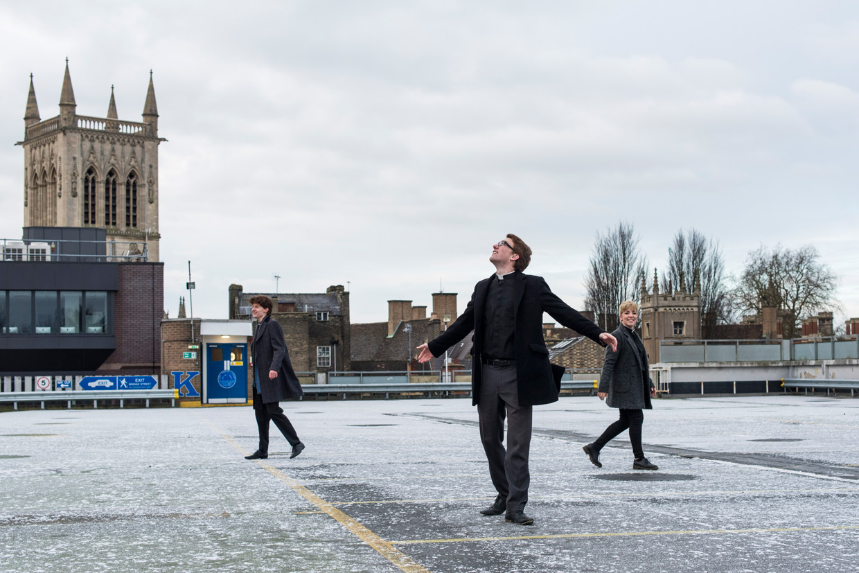Sam Knights, Oli MacFarlane and Heather Fantham on the parking lot roof with St John's Chapel in the background
