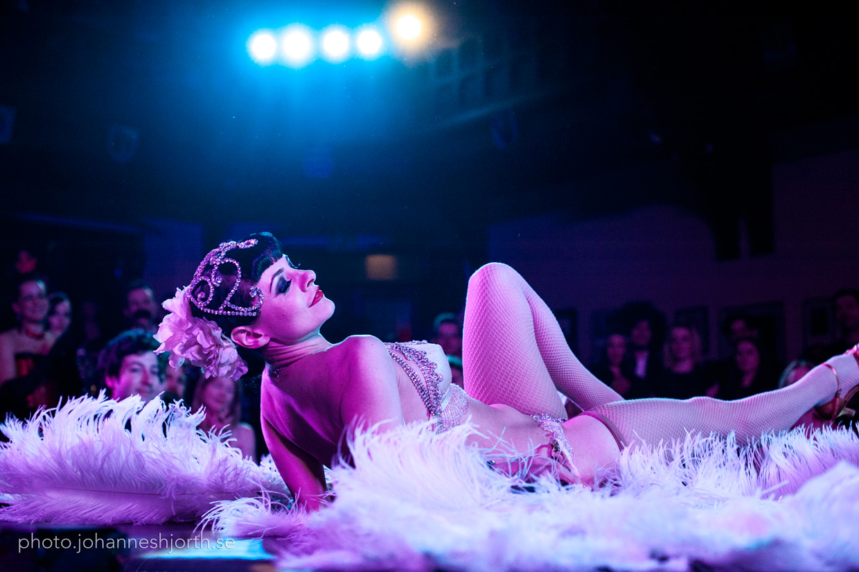 Talulah Blue lying down on stage framed by her feathers