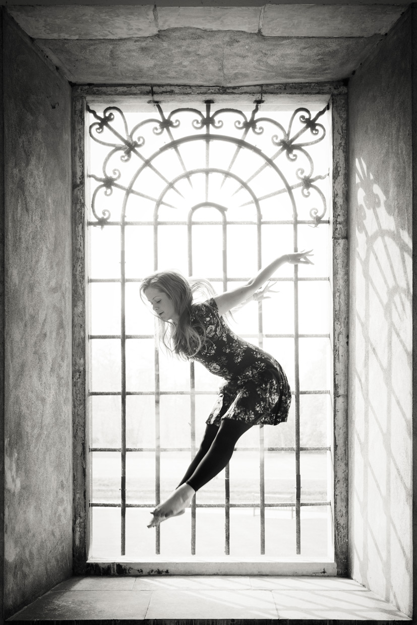 Harriet Neha Wright jumping in a window under the Wren Library at Trinity College, Cambridge.