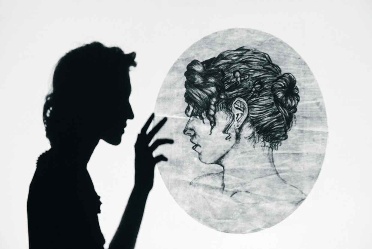 Silhouette of Hannah with one of her drawings projected on the wall