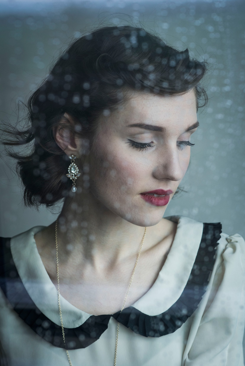 Hannah Grace Taylor photographed through a window with water droplets on it.