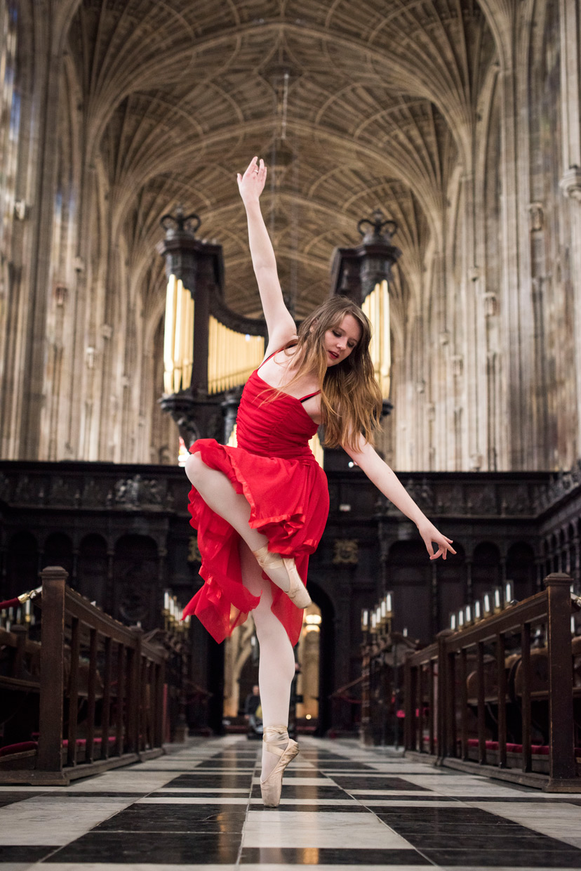 Naomi Grace in a red dress dancing in King's College Chapel.