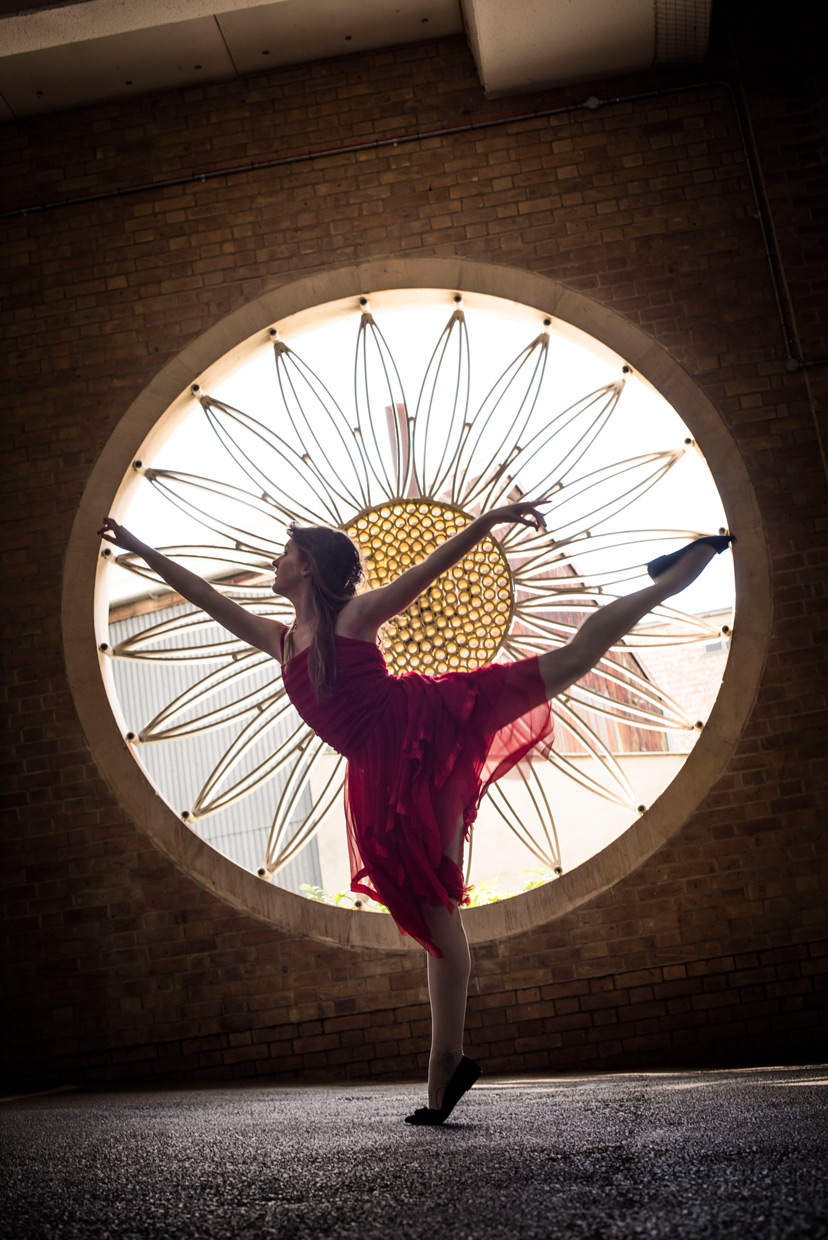 Naomi Grace doing an arabesque in the parking lot at Christ's College, with a big circular window framing her.