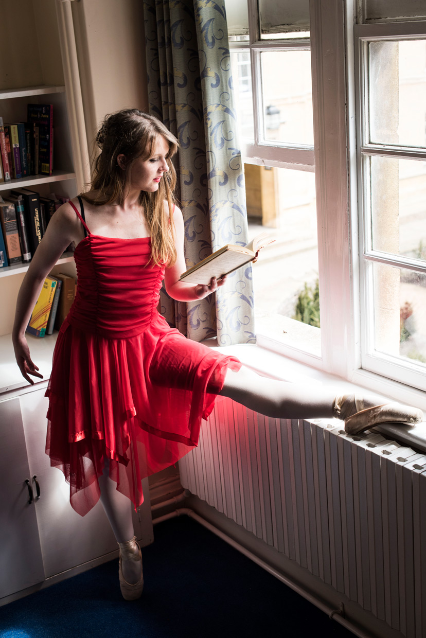 Naomi on pointe by the window reading a book.