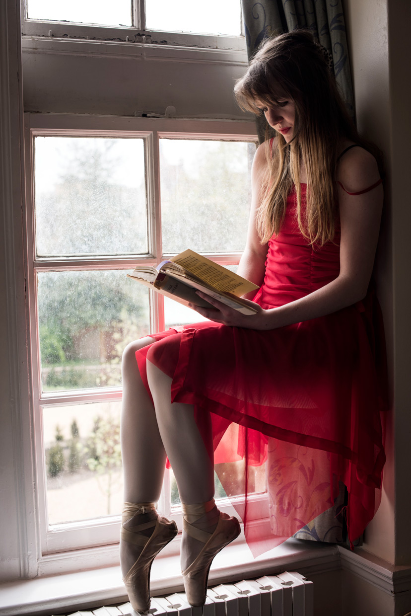Naomi on point sitting reading a book in the window.