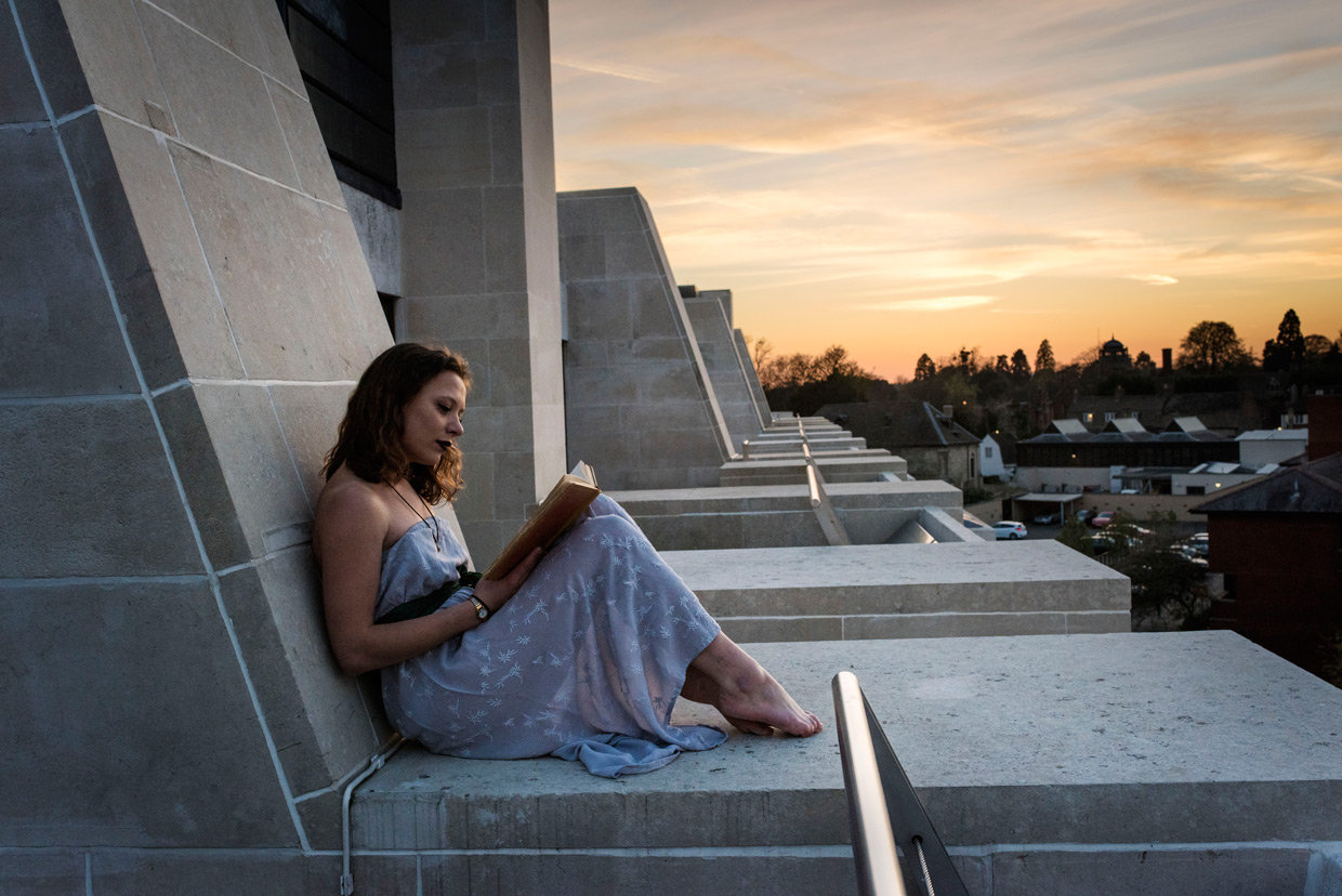 Katurah Morrish sitting reading on top of Cripps building during sunset.
