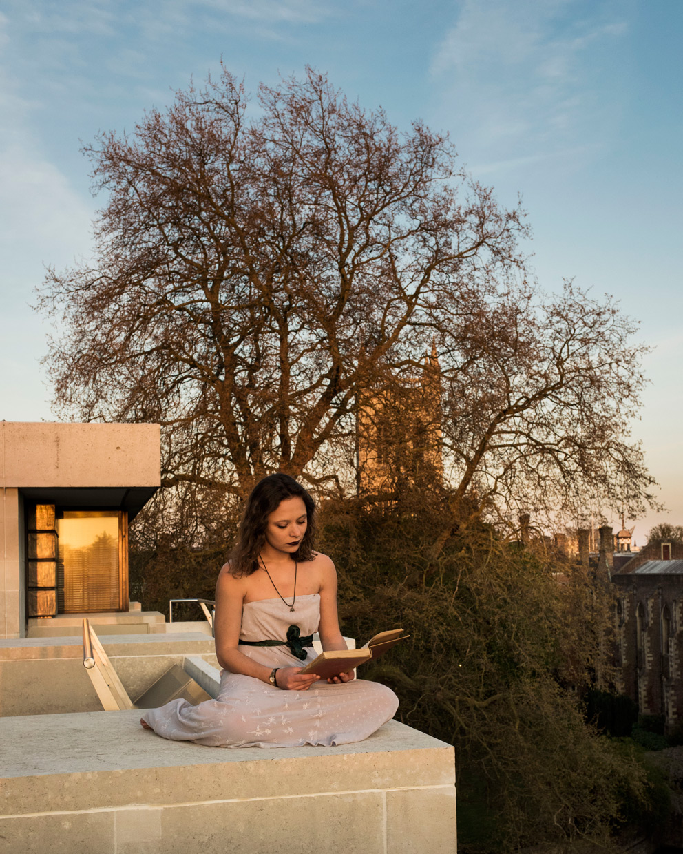 Katurah Morrish sitting on top of Cripps building reading, with St John's Chapel tower int the background.