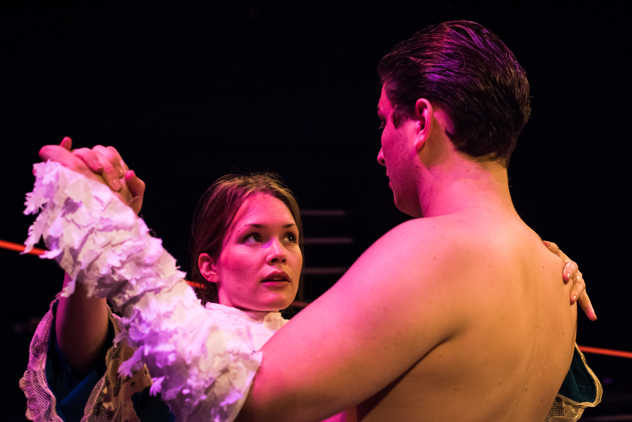Woman dancing with bare chested man wearing feathers on arms.