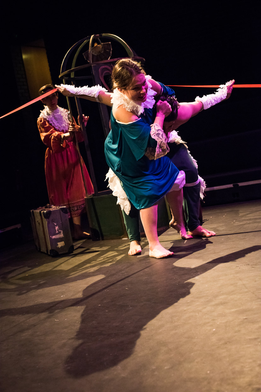 Dancing turns to wrestling as woman hooks man.