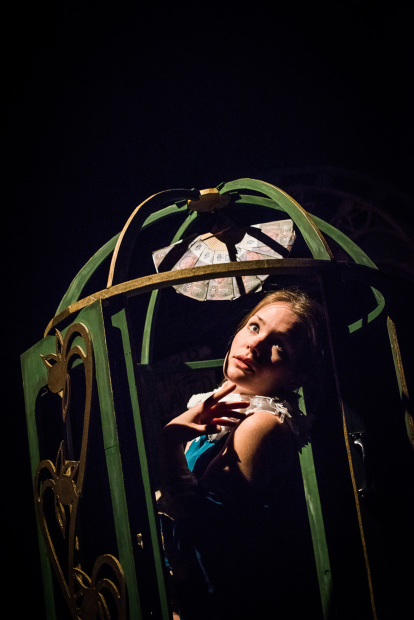 Blond woman in a wooden ornate birdcage