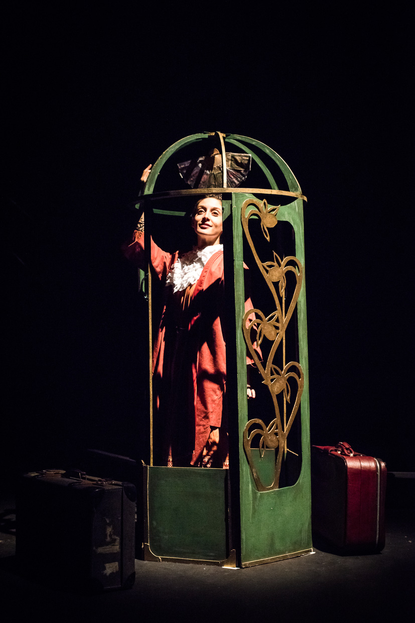 Woman in red in a wooden birdcage.