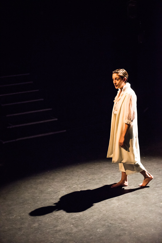 Woman walking away, dressed in white.