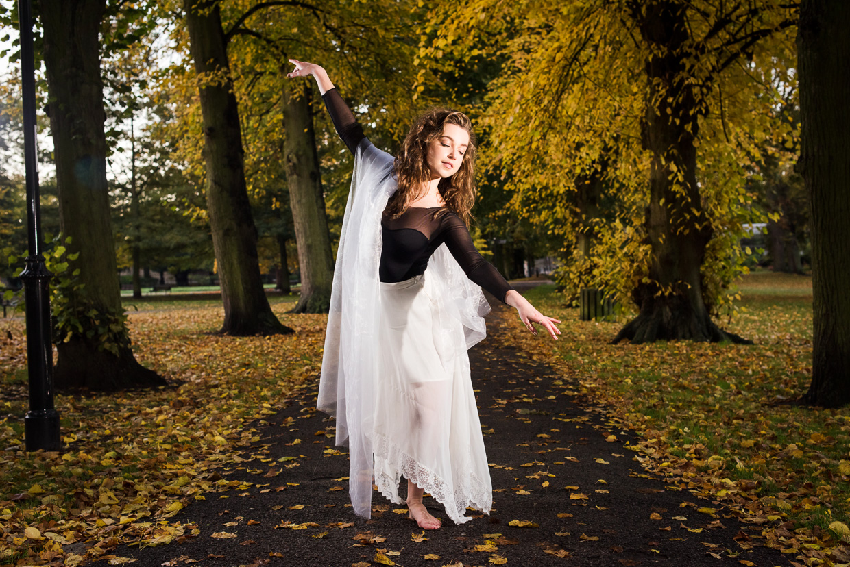 Hannah Copeland dancing, surrounded by yellow autumn leaves.