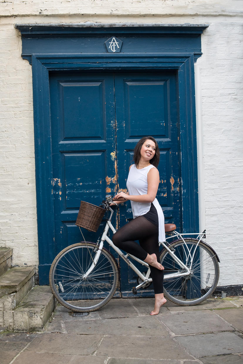Rebecca Green on a bike in front of a blue door.