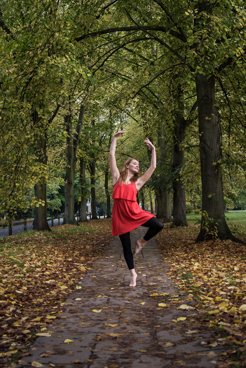 Charlie Grieco in a red dress dancing on a walking path surrounded by autumn leaves.