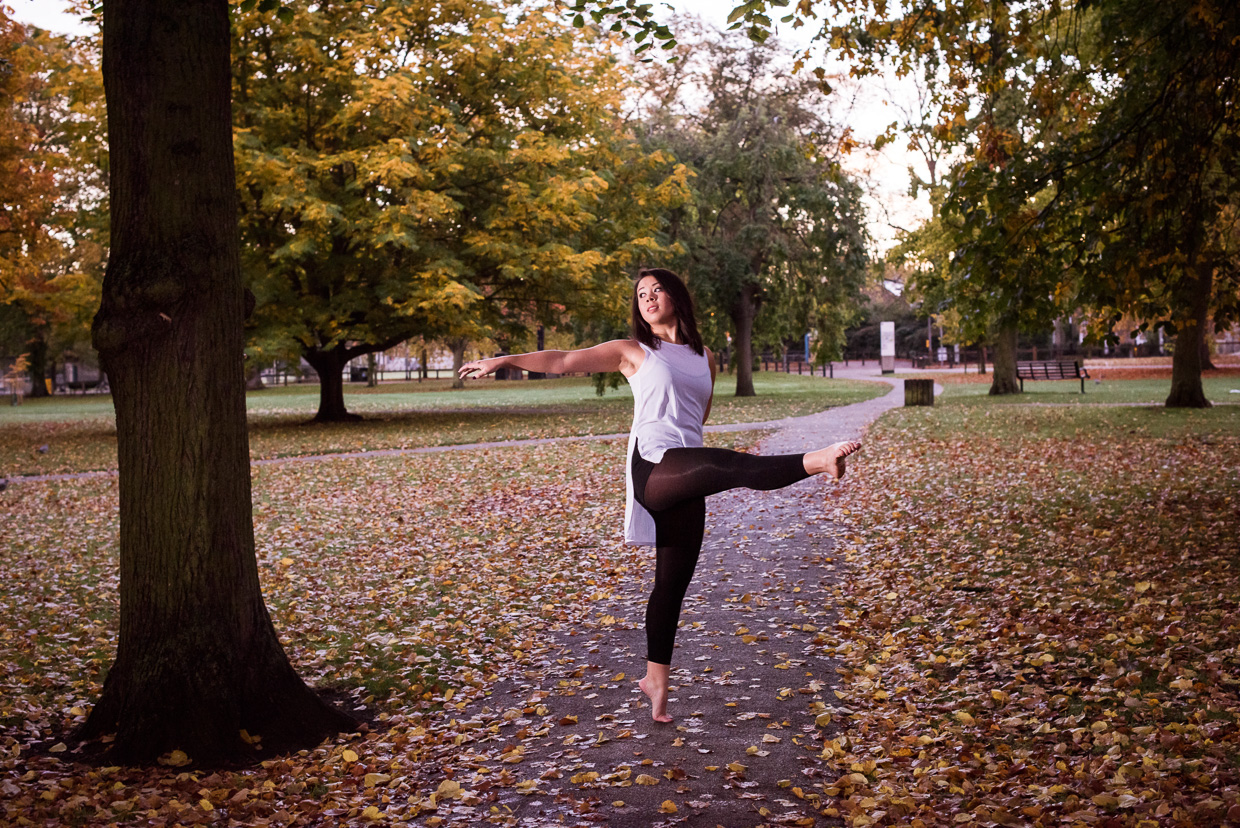 Rebecca Green dancing on a walk path covered by autumn leaves.