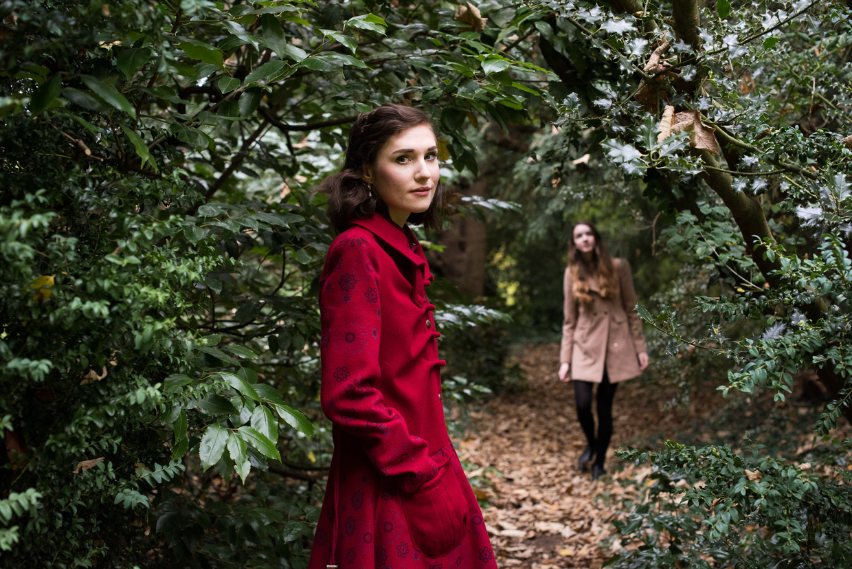 Hannah Grace Taylor wearing an elegant red coat in Peterhouse Deer Garden, with Flo Best in the background.