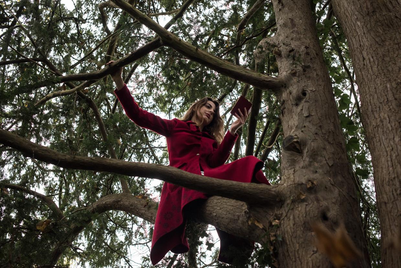 Shanti Daffern reading perched up in a tree.