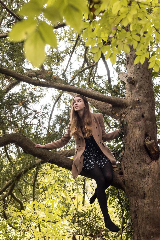 Flo Best climbing barefoot in a tree.