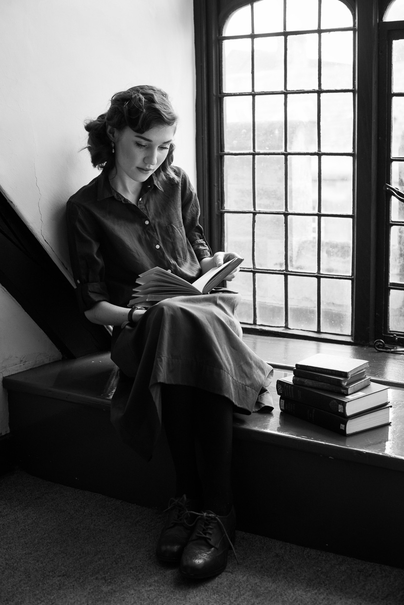 Hannah Grace Taylor sitting reading a book by the window.
