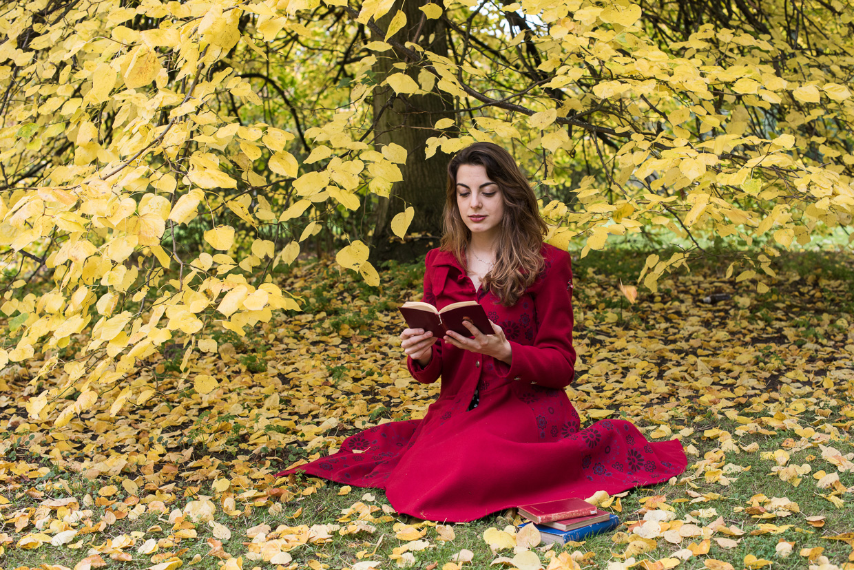 Shanti Daffern reading under a tree with lots of yellow autumn leaves around her.
