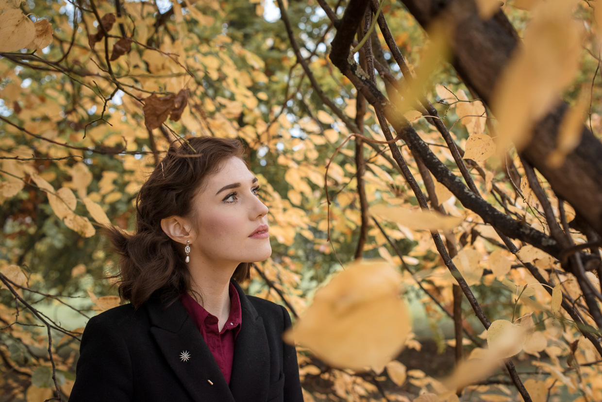 A thoughtful Hannah Grace Taylor surrounded by yellow autumn leaves at Peterhouse, Cambridge.