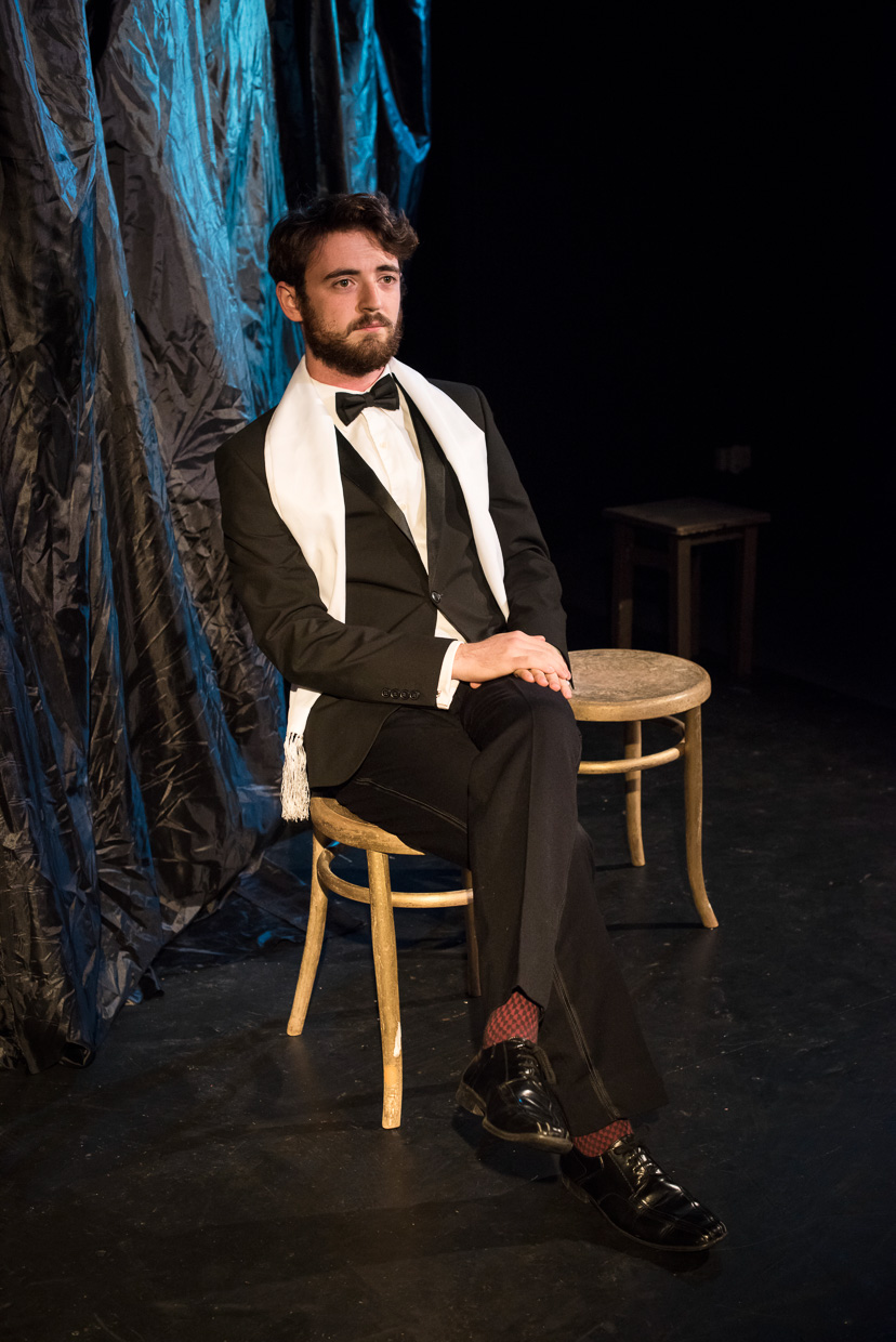 Will Bishop sitting alone dressed in a tuxedo