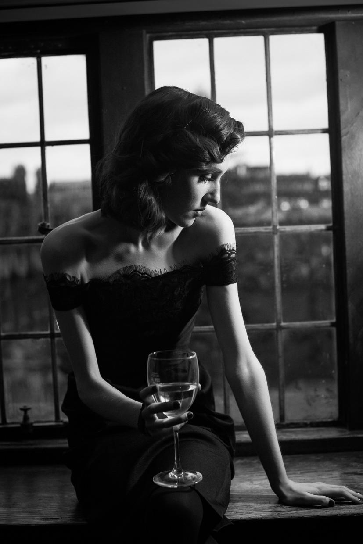Hannah Grace Taylor in black dress, sitting on window sill, drinking wine.