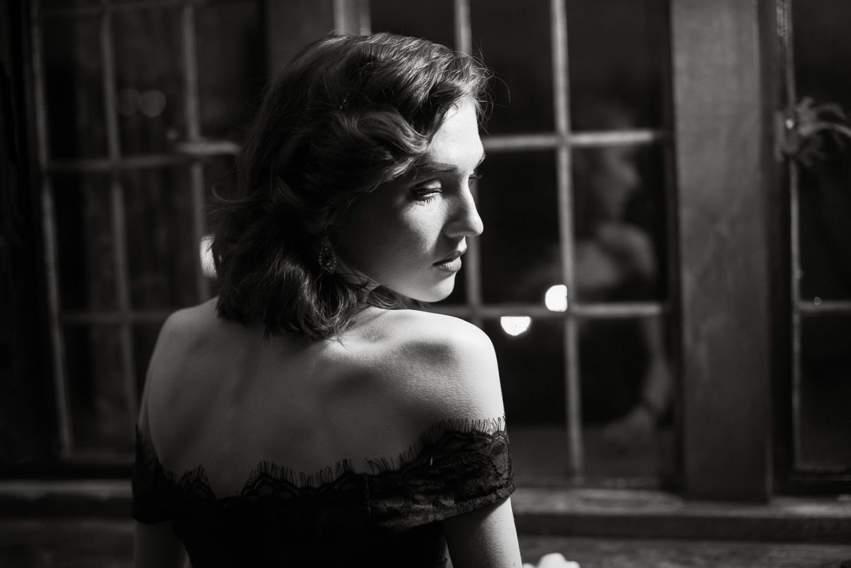Portrait of Hannah Taylor in a gorgeous black dress. Scene is lit by a single desk lamp.