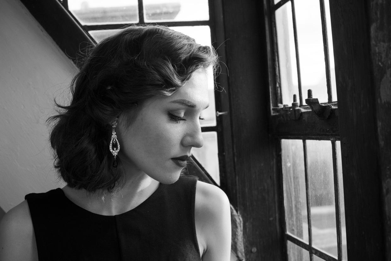 Hannah Grace Taylor by a window, eyes closed.