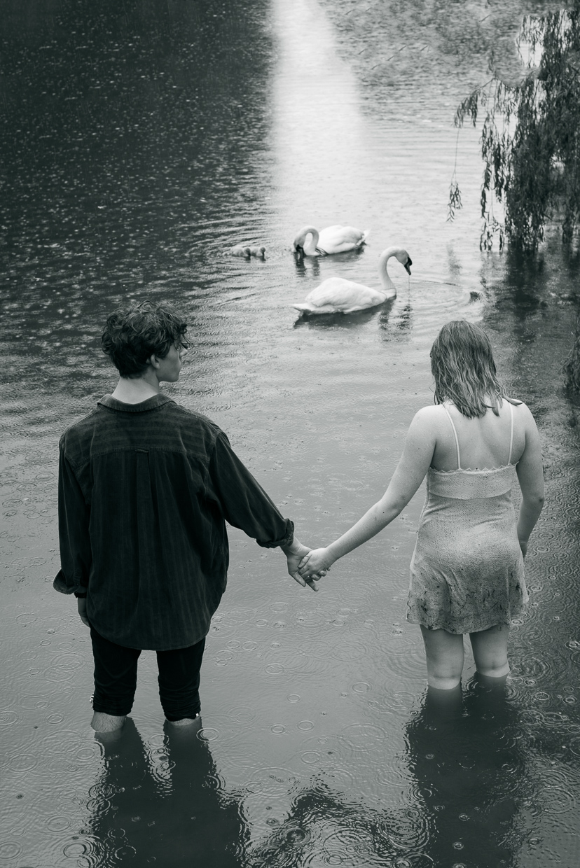 Joe and Laura hand in hand, with swans in the background.