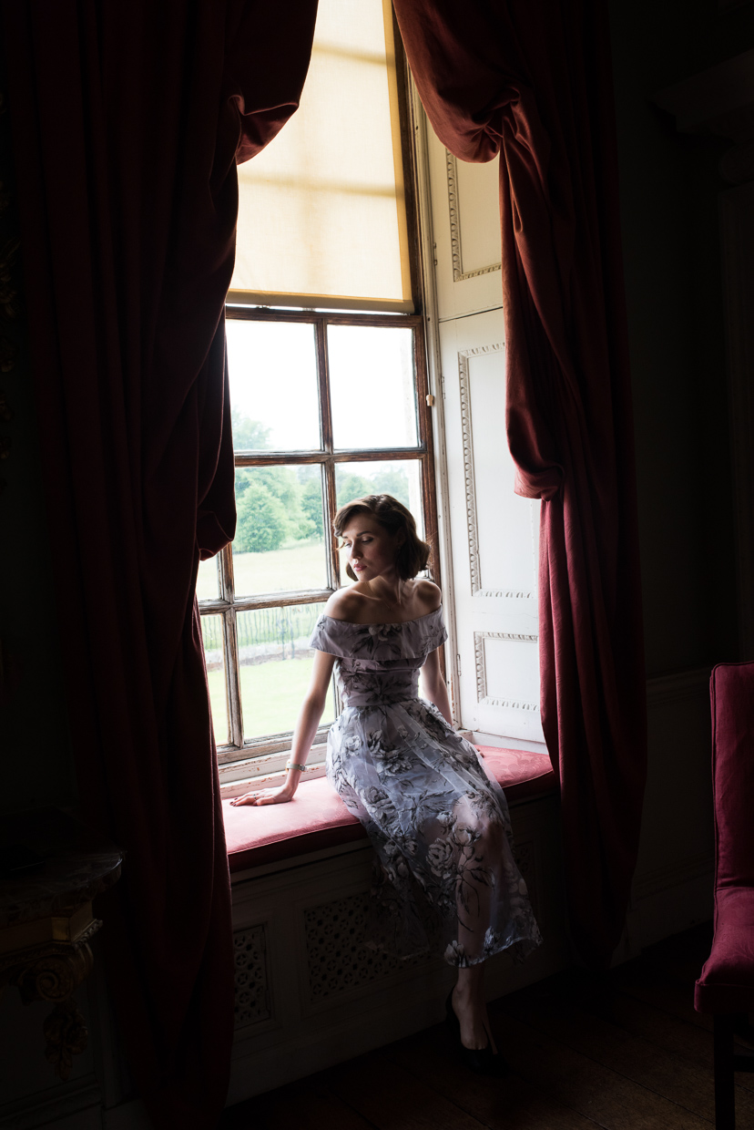 Hannah Grace Taylor sitting in a window frame at Wimpole Estate