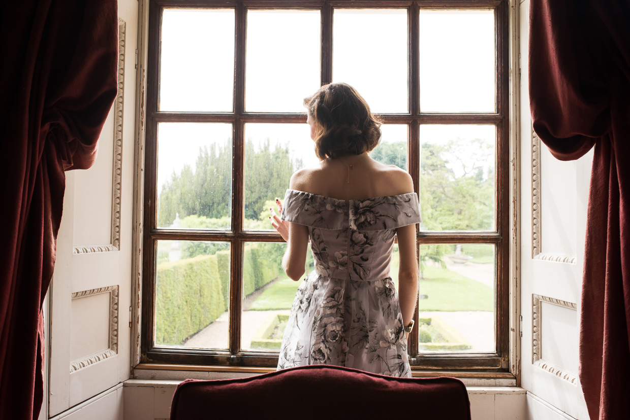 Hannah Grace Taylor looking out a window at Wimpole Estate