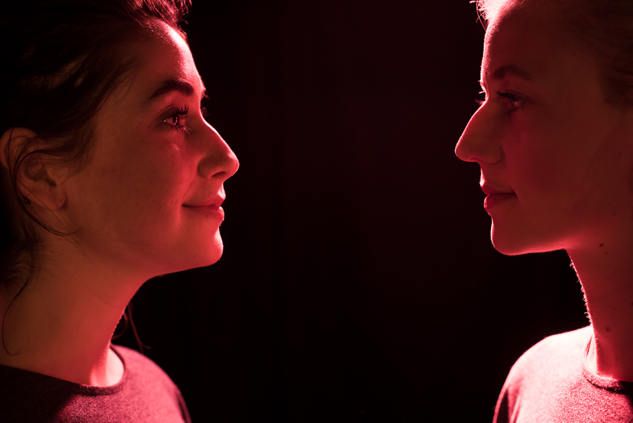 Charly Clive and Ellen Robertson facing each other, pink light on their faces.