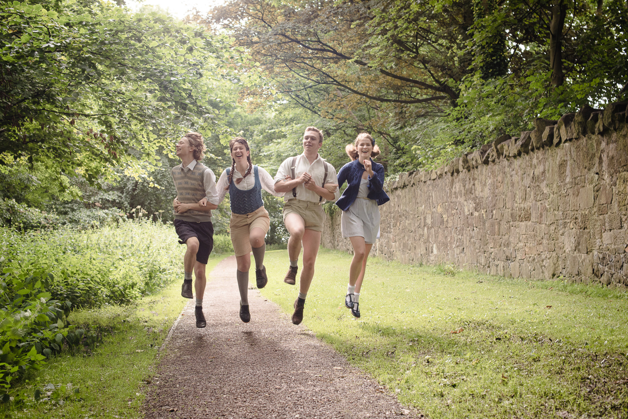 Alex Harris, Millie Foy, Sam Lamont and Molly Stacey skipping along the walking path in Edinburgh.