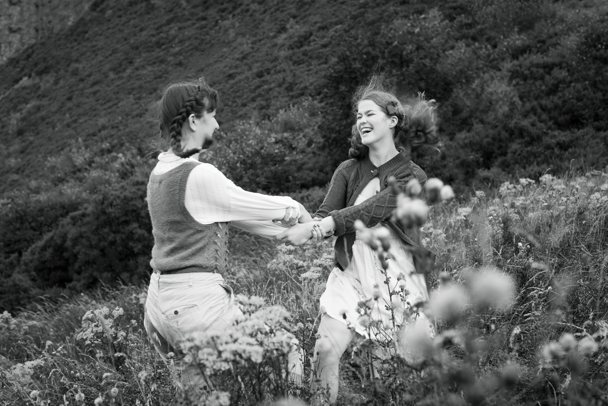 Millie Foy and Molly Stacey dancing around in a field of flowers.