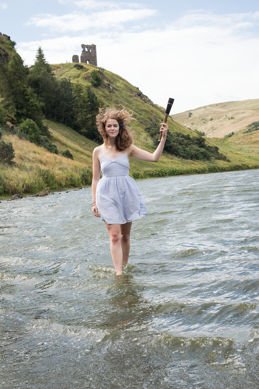 Molly Stacey at St Margaret's Loch. Walking in the water with a looking glass in her hand.