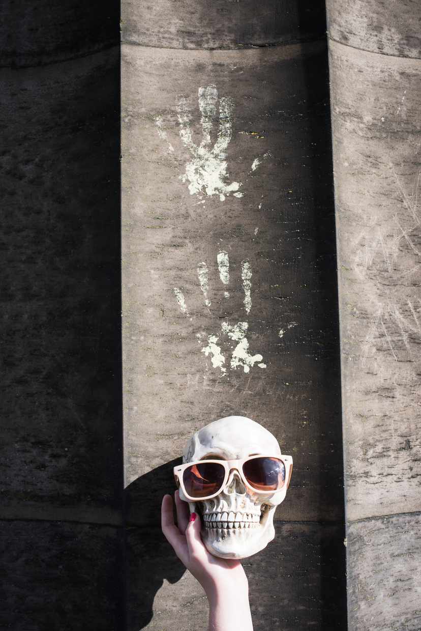 Two painted handprints and a human skull with sunglasses. Art.