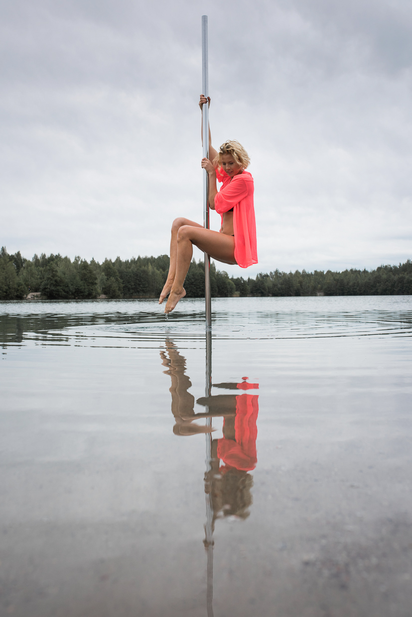 Lenita Larsson on the pole, hanging above water looking down at her own reflection.