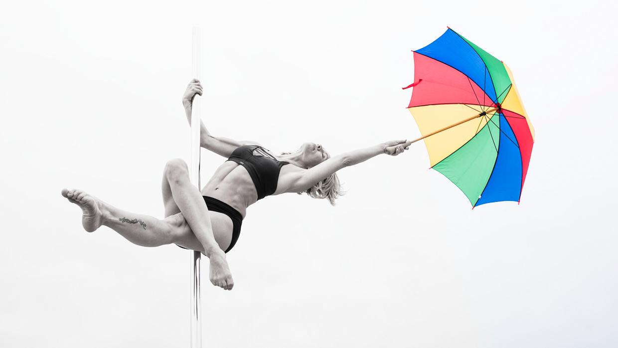 Therese Larsson on the pole dancing pole with a colourful umbrella.