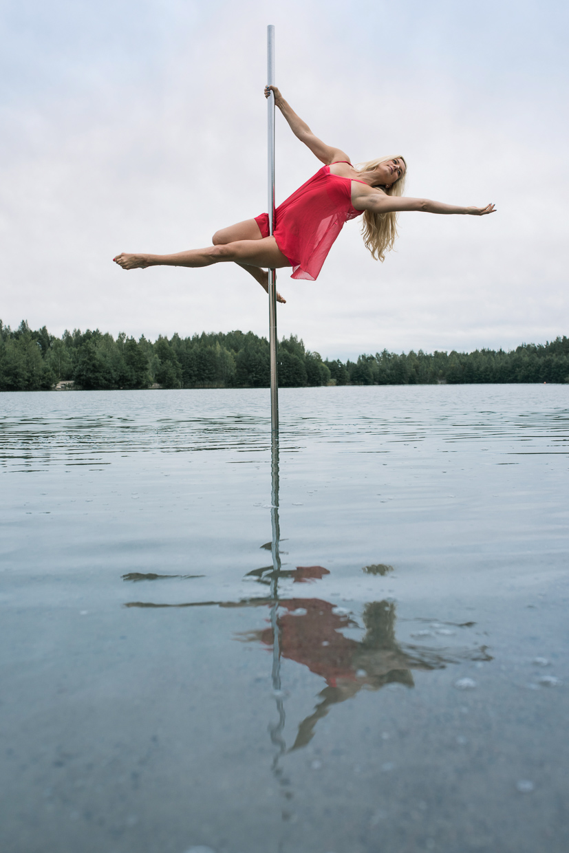 Helle Carlstedt on a pole dancing pole above water.