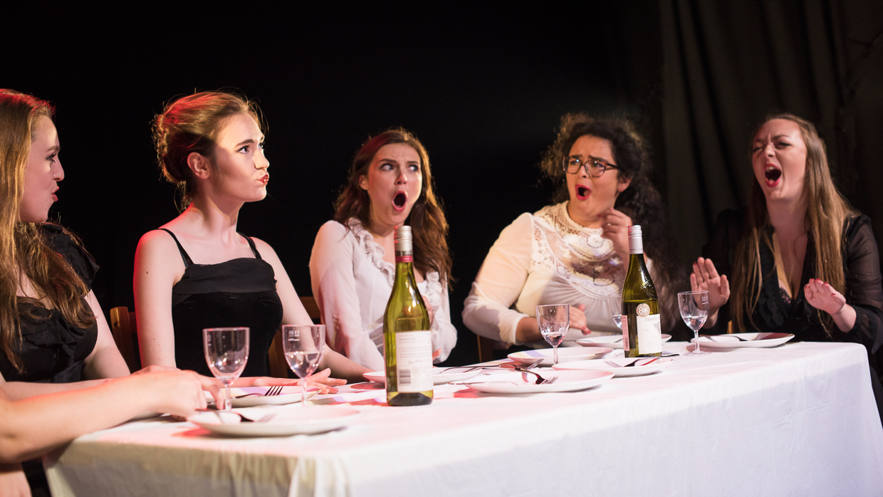 The ladies arguing at the table.