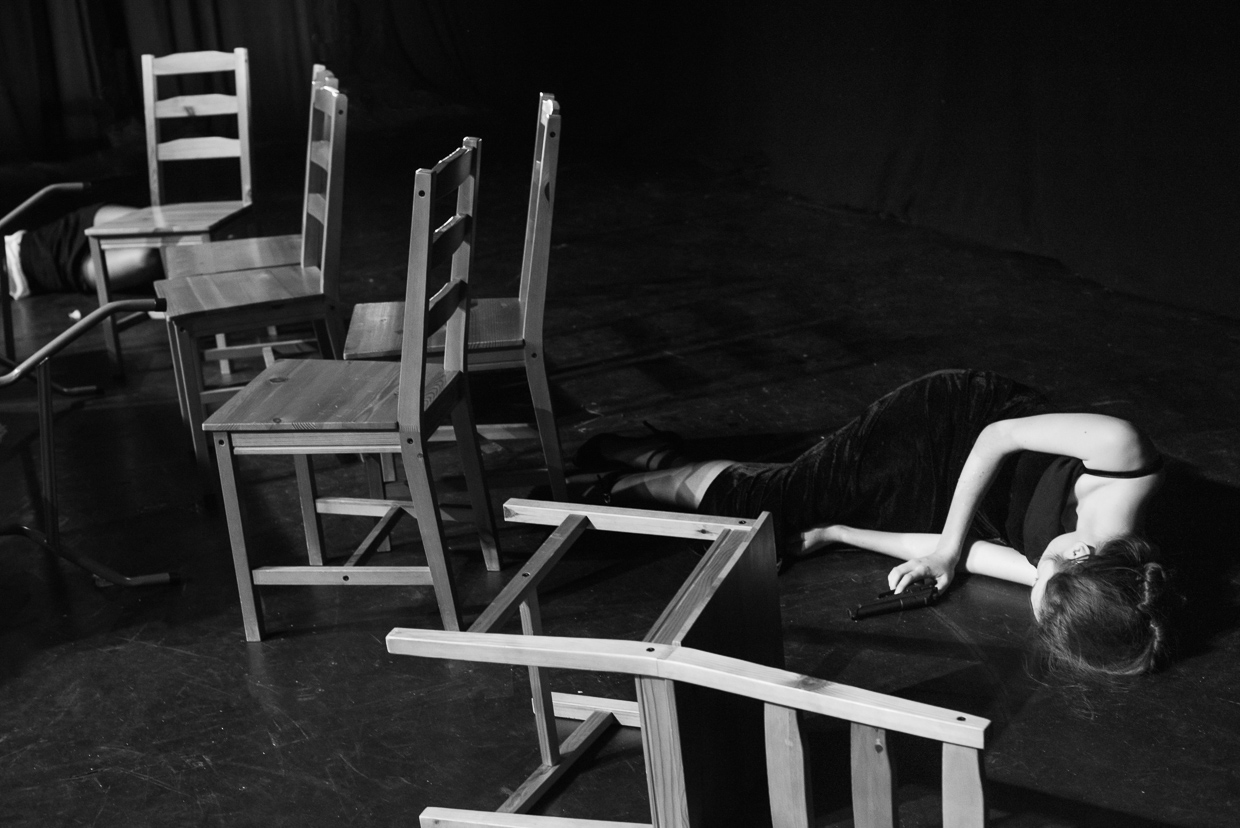 Emma gets shot, lying on the floor surrounded by chairs.