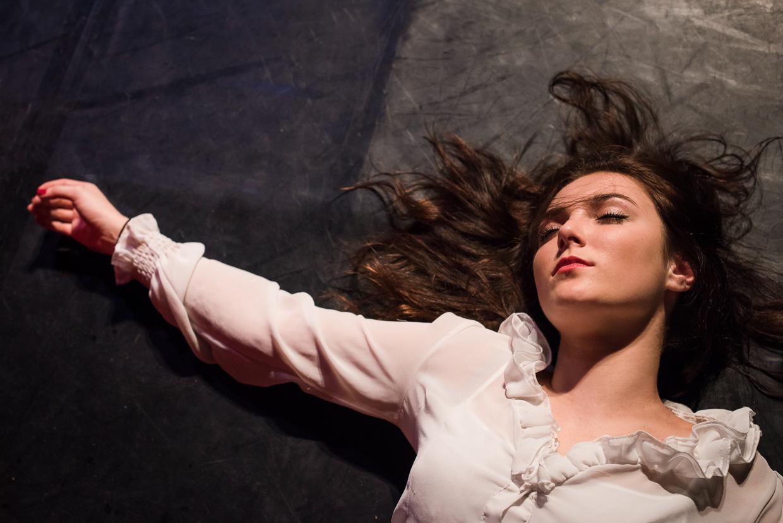 Closeup of Rebecca lying dead on the floor.