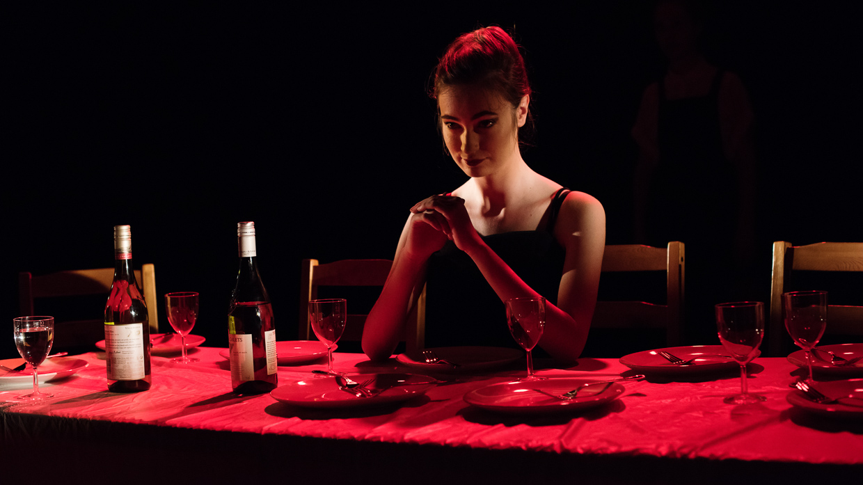 Emma Blacklay-Piech sitting at a table, bathed in red light