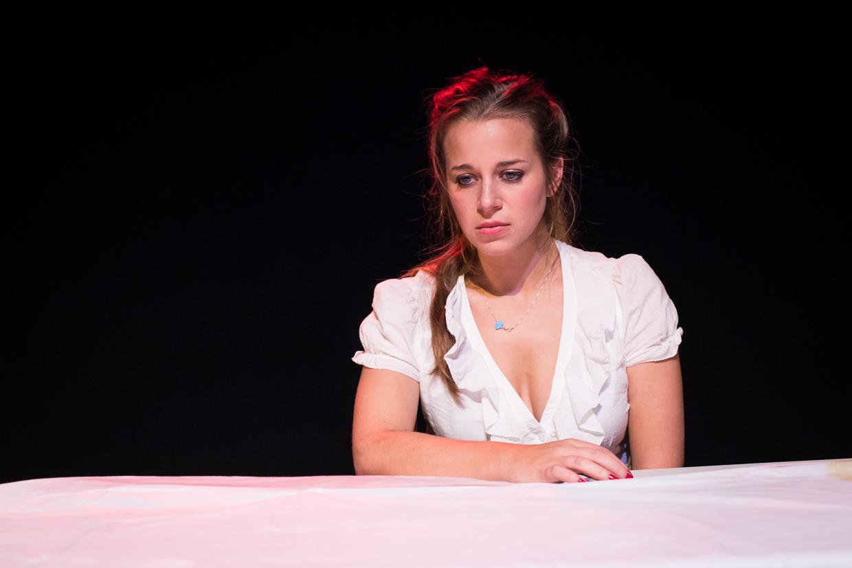 Olivia sad at the table.